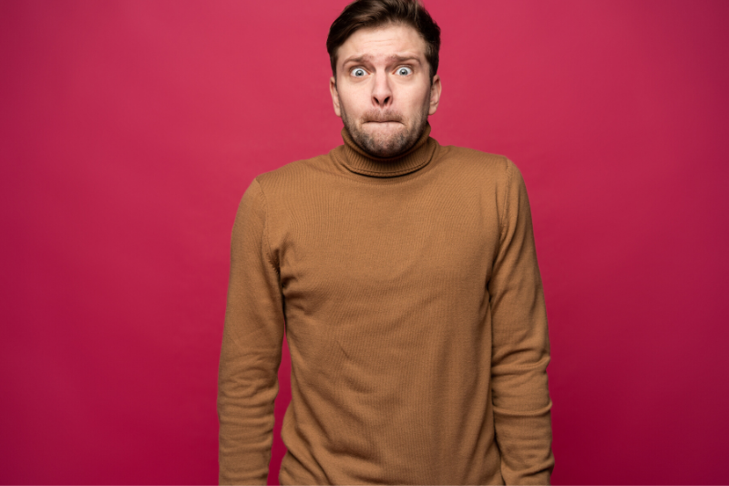 A man is standing in front of a red wall and closing his mouth