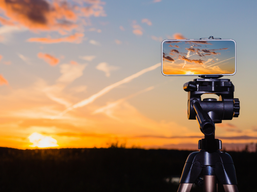 Smartphone stands with tripod to film sunset
